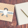 Vintage gift box on wood background with notebook and pencil. — Stock Photo #60056857