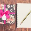 Vintage gift box on wood background with notebook and pencil. — Stock Photo #60056875