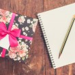 Vintage gift box on wood background with notebook and pencil. — Stock Photo #60057505