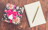 Vintage gift box on wood background with notebook and pencil. — Stock Photo