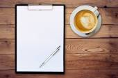 White paper clipboard and coffee on wood background with space — Stock Photo