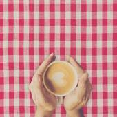 Man hand holding cup coffee on red and white fabric. — Stock Photo