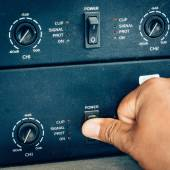 Hand turn on switch power amplifier in studio. — Stock Photo