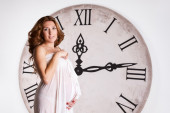 Young beautiful pregnant woman on a white background with giant cloc — Foto Stock