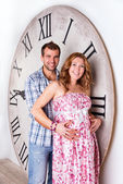 Happy Pregnant Couple on white background with giant clock — Stockfoto