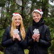 Happy young couple in love wearing Santa hats and holding big snowflakes. Man and woman celebrating Christmas and New Year — Stock Photo #58269395