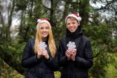 Happy young couple in love wearing Santa hats and holding big snowflakes. Man and woman celebrating Christmas and New Year — Stock Photo