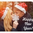 Happy young couple in love wearing Santa hats kissing and holding a big snowflake. Man and woman celebrating Christmas and New Year. Retro vintage instagram filter — Stock Photo #58270821