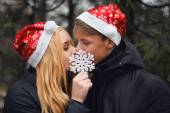 Happy young couple in love wearing Santa hats kissing and holding a big snowflake. Man and woman celebrating Christmas and New Year — Stock Photo