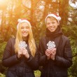 Happy young couple in love wearing Santa hats and holding big snowflakes. Man and woman celebrating Christmas and New Year. Retro vintage instagram filter — Stock Photo #58338903
