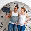 Happy Pregnant Couple dressed in white showing sign speech bubble banners looking happy excited and having idea on white background with giant clock. — Stock Photo #60531593