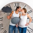 Happy Pregnant Couple dressed in white kissing and showing sign speech bubble banner looking happy excited and having idea on white background with giant clock. — Stock Photo #60536551