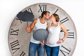 Happy Pregnant Couple dressed in white kissing and showing sign speech bubble banner looking happy excited and having idea on white background with giant clock. — Stock Photo