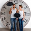 Happy Pregnant Couple dressed in white showing sign speech bubble banners looking happy excited and having idea on white background with giant clock. — Stock Photo #60542029