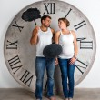 Happy Pregnant Couple dressed in white showing sign speech bubble banners looking happy excited and having idea on white background with giant clock. — Stock Photo #60589719