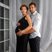 Happy Pregnant Couple dressed in black and white embrace each other by the window — Stock Photo