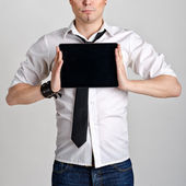 Business man holding and shows touch screen tablet pc with blank screen — Stock Photo