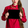 Business woman dressed in red holding and shows touch screen tablet pc with blank screen — Stock Photo #60650641