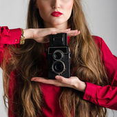 Woman in red with rarity old photographic camera closeup. — Stock Photo