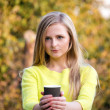 Young beautiful blonde woman offering a cup of take away coffee. Girl having a picnic at the park. — Stock Photo #64057507