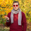 Young handsome man in red round glasses outdoor holding an apple. Walking in the woods, businessman having a break. Spring mood. — Stock Photo #64319479