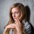 Sexy young longhair blonde woman in knitted sweater posing against grungy gray wall. Scared or resentful attractive girl hiding behind a lock of her hair — Stock Photo #64699063