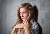 Sexy young longhair blonde woman in knitted sweater posing against grungy gray wall. Scared or resentful attractive girl hiding behind a lock of her hair — Stock Photo