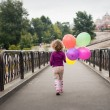 Little girl with baloons in the park — Stock Photo #64993749