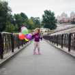 Little girl with baloons in the park — Stock Photo #65183273