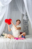 Young beautiful fashion pregnant woman sitting on the bed with toys for her baby on white background. — Stock Photo