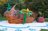 Big flower bed in a shape of basket full of different fruits with colorful chrysanthemums. Parkland in Kiev, Ukraine. — Stock Photo