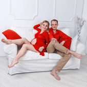 Happy young pregnant couple dressed in red embrace each other on a sofa in white living room — Stock Photo