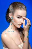 Beautiful naked young woman covered with blue crystals on blue background. — Stock Photo