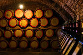 Wine barrels in the antique cellar. Cavernous wine cellar with stacked oak barrels for maturing red wine. Selective focus. — Stock Photo