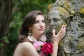 Beautiful young nude woman with an antique statue and bouquet of flowers. Comparison of lively female beauty and art of the ancient sculptors. — Stock Photo