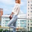 Outdoor summer fashion stunning portrait on pretty young blonde sexy woman dressed in a white shirt and torn jeans having fun in the street — Stock Photo #74222469