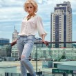 Outdoor summer fashion stunning portrait on pretty young blonde sexy woman dressed in a white shirt and torn jeans having fun in the street — Stock Photo #74222483
