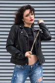 Glamorous young brunette woman in black leather jacket and golden chain in her hands having fun in the city. — Stock Photo