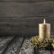 Golden burning advent candle on wooden nostalgic background. — Stock Photo #52364329