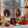Christmas window decoration: candles with old children toys. — Stock Photo #52509621