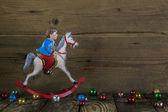 Old christmas decoration of tin: rocking horse on wooden backgro — Stock Photo