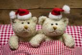 Lovers: two teddy bears sitting on christmas with hats in the be — Foto Stock