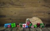 Many colorful christmas presents on wooden old background. — Stok fotoğraf