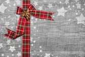 Festive grey wooden christmas background with a red ribbon. — Stockfoto