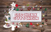 Wooden colorful christmas sign with text and decoration: gift ce — Stockfoto