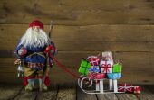 Santa Claus with slide of presents on wooden background for chri — Stock Photo