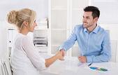 Handshake: Adviser says hello to his female customer. — Stock Photo
