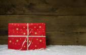 One red christmas present with golden stars on wooden snowy back — Stockfoto