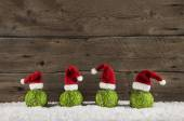Funny christmas background with green balls and santa hats on wo — Stock Photo