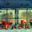 Old wooden window decorated for christmas with red candles and p — Stock Photo #55047271